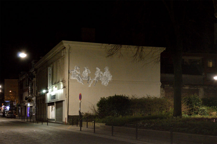 La fontaine Watteau s'illumine à la tombée de la nuit tandis que sur la façade, toute proche, quatre personnages en costume d'époque s'éclairent...